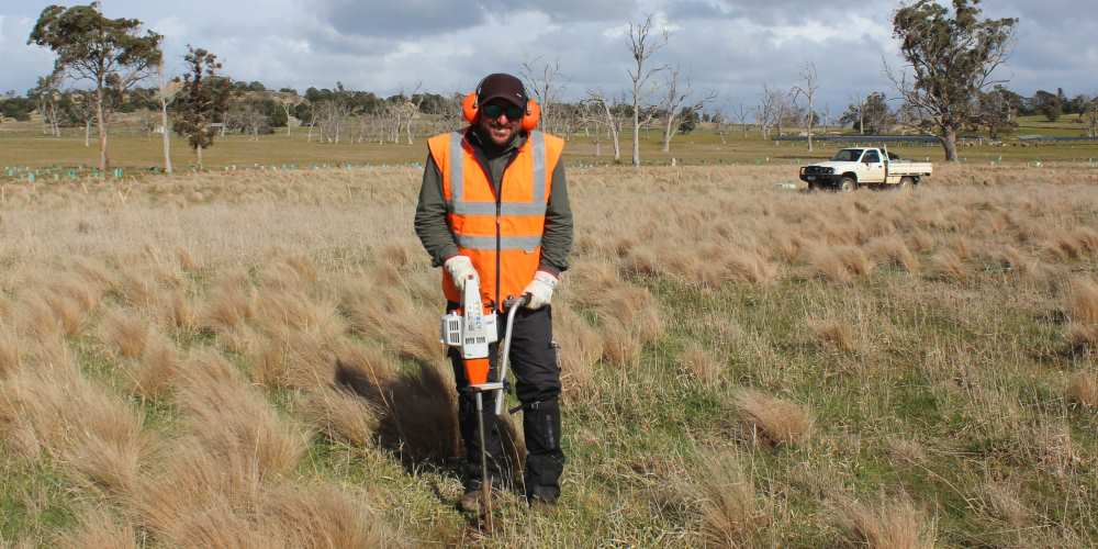 tree planting site preparation man with auger Australia